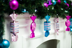 Glass Christmas candy hanging on the mantelpiece. Glass Christmas candy hanging from a garland on the mantelpiece Royalty Free Stock Images