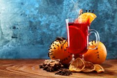 Glass of christmas hot mulled wine on wooden table with species and oranges against frozen window.Copy space.  royalty free stock photos