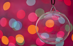 Glass Christmas Ornament against multi colored lights Royalty Free Stock Image