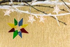Glass christmas star hanging on tree branch Stock Photos