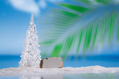 Glass christmas tree on  beach with seascape background Stock Photos