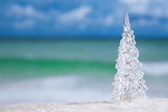 Glass christmas tree on  beach with seascape background Royalty Free Stock Images