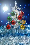 Glass christmas tree with colorful balls on blurred lights background Stock Photos