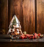 Glass Christmas tree with cookies and decoration on rustic wooden background Royalty Free Stock Photography