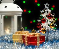 Glass fir-tree and white lantern standing in blue tinsel with christmas decorations on background with blurred lights. Glass christmas tree and white glowing royalty free stock photo