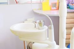 Glass chromium on Sink medical equipment dentist Close up, ceramic spittoon and water filler in Clinic royalty free stock photos