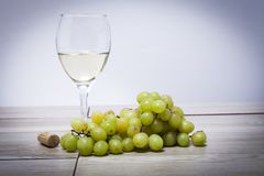 Glass cup on the table grapes and cork. Glass of cider on the table with green grapes and cork decoration Royalty Free Stock Photography