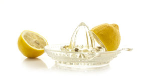 Glass citrus squeezer with lemons. And juice on a white background Royalty Free Stock Photos