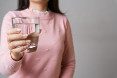 A glass of clean mineral water in woman`s hands. Concept of environment protection, healthy drink and healthcare.  stock photo