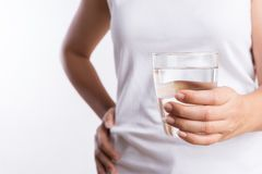 A glass of clean mineral water in woman`s hands. Concept of environment protection, healthy drink and healthcare.  royalty free stock photos