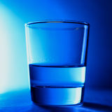 Glass of clean water close-up on a blue background isolated with ice in the form of a polar bear. A glass of clean water close-up on a blue background isolated Stock Photos