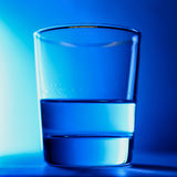 Glass of clean water close-up on a blue background isolated with ice in the form of a polar bear. A glass of clean water close-up on a blue background isolated Royalty Free Stock Image