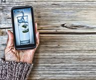 A glass of clean water in the display. A smartphone in a woman with a picture of a glass of clean water in the display. Concept: healthy lifestyle, diet, beauty Stock Photography
