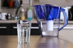 Glass of clean water and filter for cleaning drinking water on the table in the kitchen. Purification of drinking water at home.  stock image