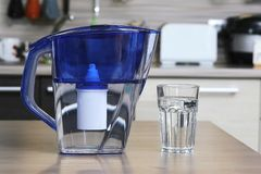 Glass of clean water and filter for cleaning drinking water on the table in the kitchen. Purification of drinking water at home.  royalty free stock photography