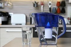 Glass of clean water and filter for cleaning drinking water on the table in the kitchen. Purification of drinking water at home.  stock photo