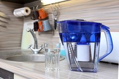 Glass of clean water and filter for cleaning drinking water on the table in the kitchen. Purification of drinking water at home.  stock images
