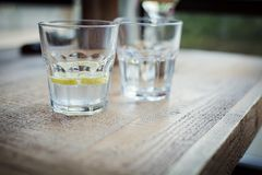 Glass of clean water with lemon. A glass of clean water with lemon on a wooden table by the window Royalty Free Stock Images