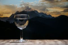 A glass glass glass with clean water stands on a wooden table against a mountain landscape. Stock Photos