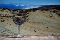 A glass glass glass with clean water stands on a wooden table against a mountain landscape. Stock Photo
