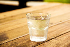Glass of clear alcohol on wooden table Royalty Free Stock Images
