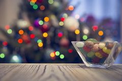A bowl of candies on a wooden table against decorated Christmas tree stock photography
