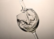 Clean water pours into the glass. A glass of clear clear water for drinking - bryzki and drops Royalty Free Stock Photo
