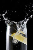 Glass of clear drink with a slice of lemon. stock images