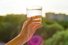 Glass of clear, ecology water in hand. Background sky, silhouette of the city, sunset.  Royalty Free Stock Images