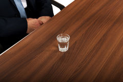 Glass of clear vodka on the desk Royalty Free Stock Photo