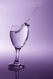 Glass with clear water falling over to spill with purple back li Royalty Free Stock Photo