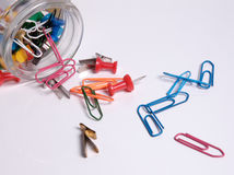 Glass with clips and pins. Paper clips and pins on white ground Royalty Free Stock Image