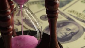 Glass clock with sand. Close up. Glass clock with sand, sand flowing through an hourglass, glass clock standing on the dollar bills, sand pink, time is sand stock video footage