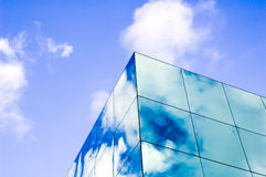 Glass clouds. Modern glass building with square panes of glass reflecting clouds and blue sky Royalty Free Stock Image