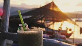 Glass of cocktail on the beach cafe at sunset time and boats in the sea. 1920x1080. Hd stock footage