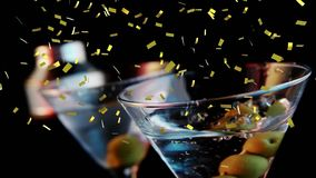 Glass of cocktail and confetti. Digital composite of olives dropped on a glass of cocktail while gold confetti fall in the screen royalty free illustration