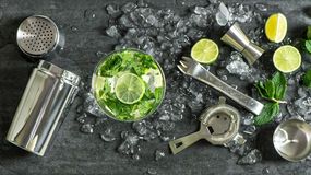 Glass cocktail lime, mint, ice. Drink making bar tools shaker. Glass of cocktail with lime, mint, ice. Drink making bar tools, shaker, ingredients stock photo
