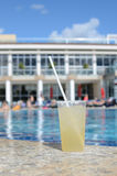 A glass with a cocktail near the swimming  pool Royalty Free Stock Images