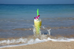 Glass Of Cocktail In The Sand Splashed By Waves Stock Photo