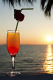 Glass with cocktail and a straw against blue sea, sky and sunset Royalty Free Stock Images