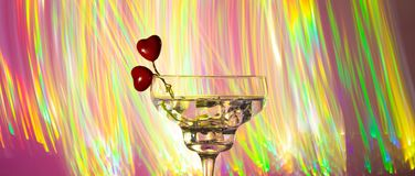Glass with a cocktail and two hearts. Valentine`s day and wedding concept. On a dark pink background with light highlights royalty free stock photography