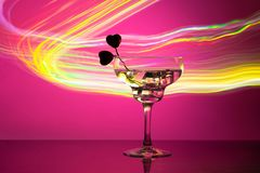 Glass with a cocktail and two hearts. Valentine`s day and wedding concept. On a dark pink background with light highlights royalty free stock images
