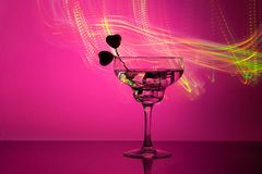 Glass with a cocktail and two hearts. Valentine`s day and wedding concept. On a dark pink background with light highlights stock image