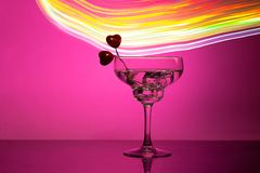 Glass with a cocktail and two hearts. Valentine`s day and wedding concept. On a dark pink background with light highlights stock photos