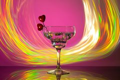 Glass with a cocktail and two hearts. Valentine`s day and wedding concept. On a dark pink background with freezelight stock images