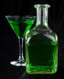 Glass of cocktails. Glass of green cocktails and bottle on black Stock Image