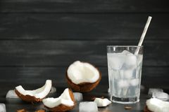 Glass of coconut water and fresh nut. On dark wooden background Stock Photography