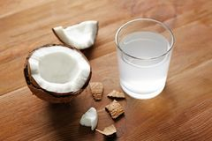 Glass of coconut water and fresh nut. On wooden background Stock Photo