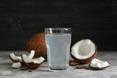 Glass of coconut water and fresh nuts. On dark background Stock Photos