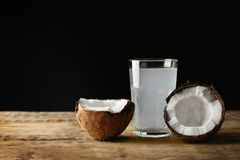 Glass of coconut water with nut. On wooden table royalty free stock photo